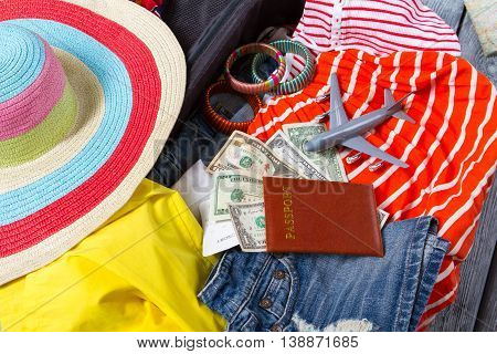 Passport with dollars on clothes. Striped bracelets and beach hat. Go travelling this summer. Personal document and plane ticket.