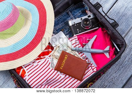 Camera in suitcase with clothes. Dollars and toy plane. Season of vacation. Everything is ready for flight.