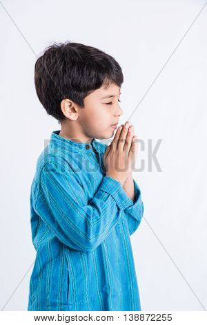 Portrait of Indian Boy Praying in traditional cloths, isolated over white background