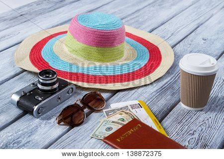 Beach hat and passport. Cup with lid near sunglasses. Morning coffee before trip. Be ready for new impressions.