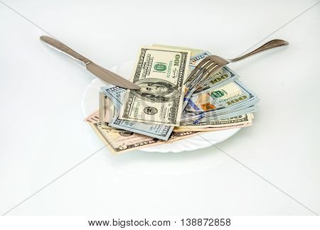 US currency on a plate with knife and fork