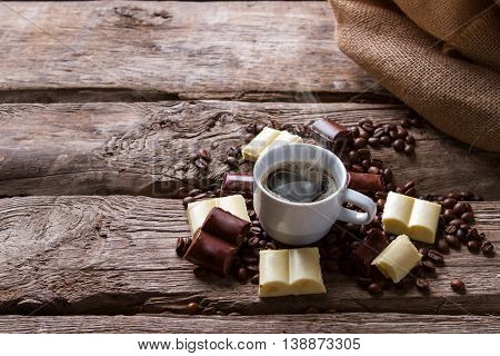 Steaming cup of coffee. Coffee grains near a bag. Hot drink and sweet chocolate. Have a cup of americano.