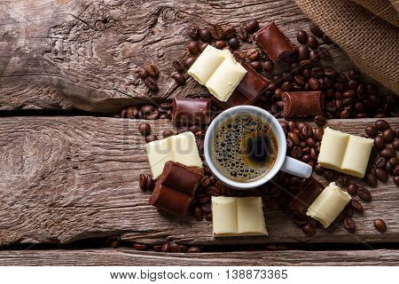 Chocolate and cup of coffee. Coffee grains and dark chocolate. High amount of caffeine. Hot beverage for dessert.