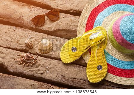 Seashells and yellow flip flops. Lady's sunglasses near a hat. Spend vacation at the sea. Warmth of summer sun.