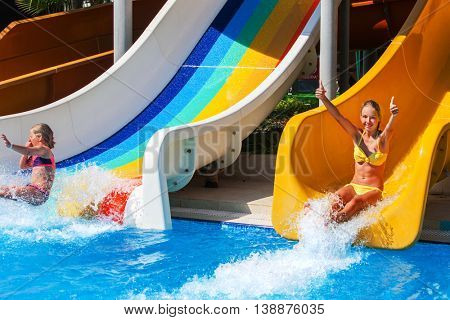 Two children on water slide at aquapark and hands up. Summer holiday. There are two water slides in aqua park. Outdoor. Water children summer holiday.