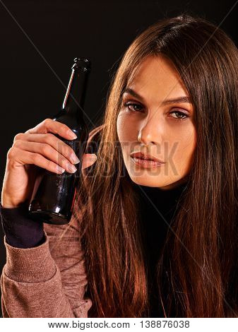 Drunk girl drink alcohol from bottle of alcohol on black background. Soccial issue female alcoholism.