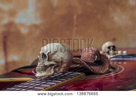 Skull and hat on a background of classical guitar.