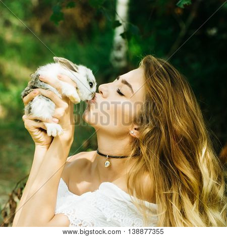 Pretty Young Woman Kisses Rabbit