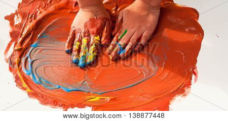 the small child of preschool age draws on paper hands and palms