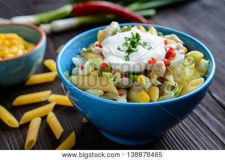 Penne pasta salad with fried chicken meat, lettuce, red pepper, scallion and sour cream dressing