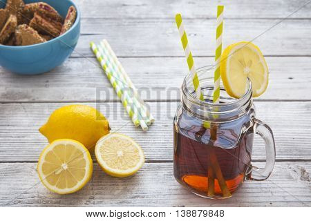 Iced tea with lemon slices and raspberry chip cookies on rustic background. Focus on ice tea