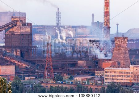 Industrial landscape in Ukraine. Steel factory at sunset. Pipes with smoke. Metallurgical plant. steelworks iron works. Heavy industry in Europe. Air pollution from smokestacks ecology problems.