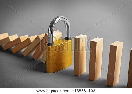 Lock blocked row of falling dominoes on grey background