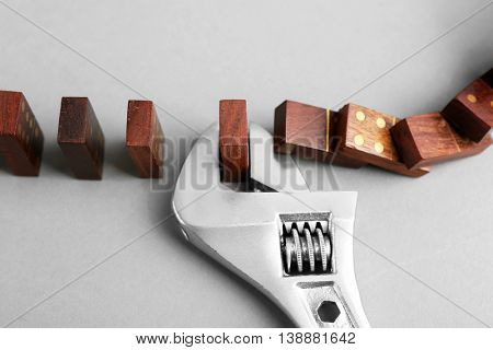 Dominoes and wrench on grey background