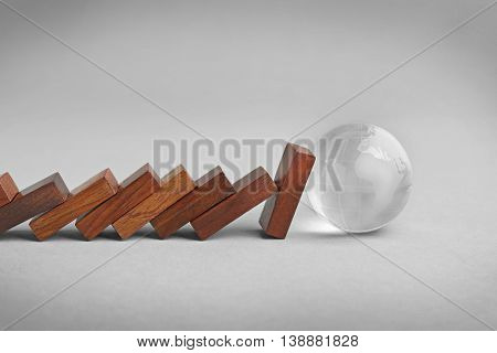 Dominoes and transparent earth ball on grey background