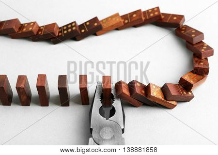Dominoes and pliers on grey background