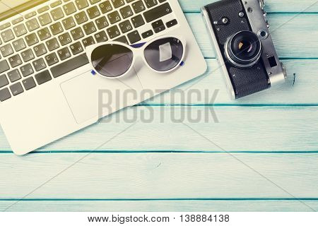 Desk table with laptop and camera on wooden table with sun beam. Workplace. Top view with copy space.