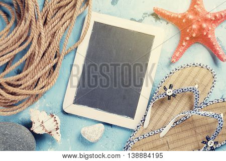 Beach vacation background. Flip-flops, seashells and blackboard for your text over stone backdrop. Top view with copy space. Sunny toned