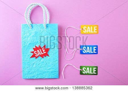 Paper bag with tags and word sale on pink background
