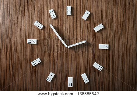 Dominoes in clock shape on wooden table