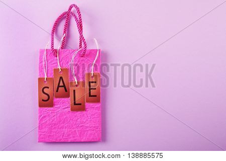Paper bag with word sale on pink background