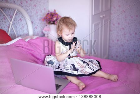 baby in pink room sitting on the bed and playing or watching cartoons price. Girl sitting at home. little princess in dress uses advanced fashion technology