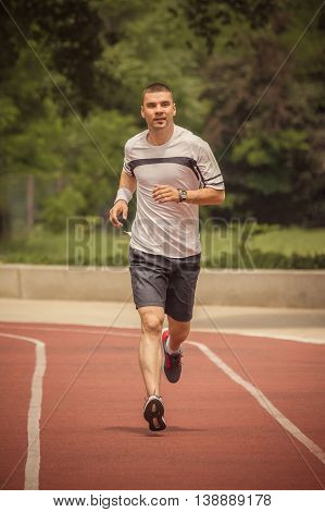 Morning training. Jogger running on the red running track. Workout, sport, healthy lifestyle concepts.