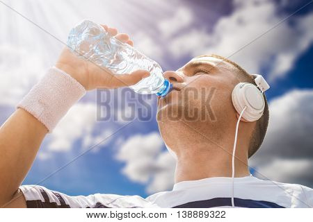 Portrait of thirsty sportsman drinking water from the plastic bottle after morning training. Low angle shot. Blue sky, sunrays and clouds in the background. Ideal for bottle pack shoot adding. Sport, recreation, workout and healthy lifestyle concepts.