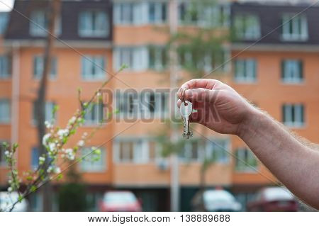 man's hand holding the keys to the apartment on the background of a multistory building.