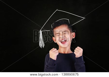 Success concept portrait of happy young Asian student boy showing enthusiastic winning gesture shout with joy of victory over blackboard with graduation hat drawn above his head