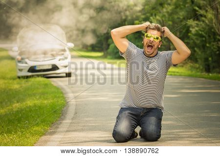 Young man on his knees on the road. He is under stress and pulling his hair out because his car is broken and in smoke. Travel and vacation road problems and assistance concepts.