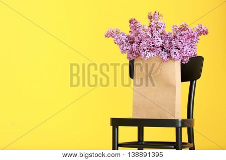 Bouquet of purple lilac flowers in paper bag on yellow background