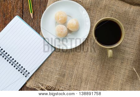 Coffee and sweetmeat with notebook on Sackcloth brown.Top view focus.