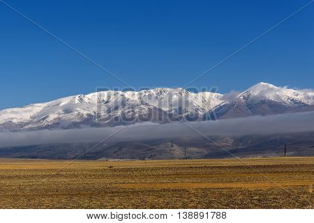 Beautiful steppe autumn view of the mountains covered with snow and a tubular cloud on a background of blue sky and beautiful little fluffy clouds