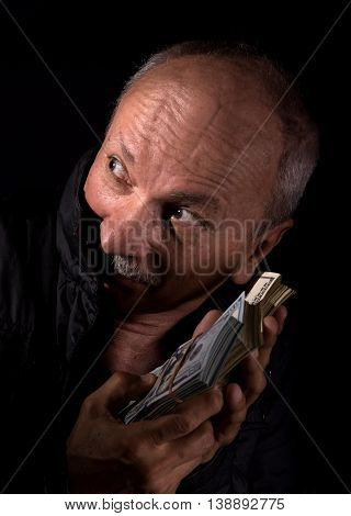 Sly senior man holding dollar bills on a dark background