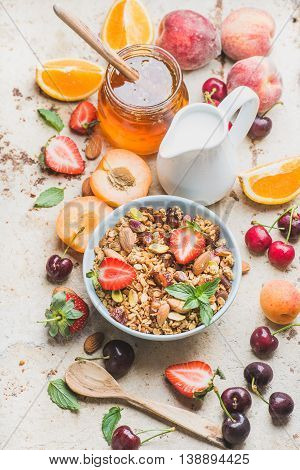 Healthy breakfast ingredients. Oat granola in bowl with nuts, strawberry and mint, milk in pitcher, honey in glass jar, fresh fruits and berries on light concrete background, top view, selective focus, horizontal composition