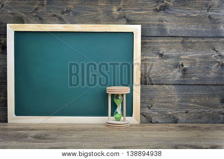 School board and hourglass on wooden table