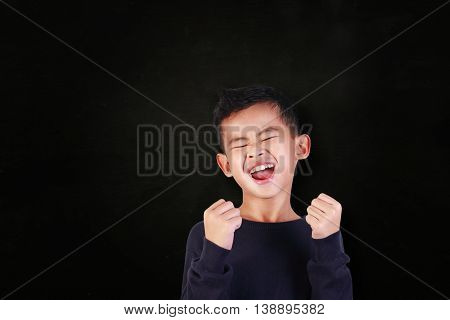 Success concept portrait of happy young Asian boy showing enthusiastic winning gesture shout with joy of victory over blackboard