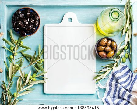 Two bowls with pickled green and black olives, olive tree sprigs and bottle of olive oil with white ceramic board in center. Blue Turquoise background, copy space, top view