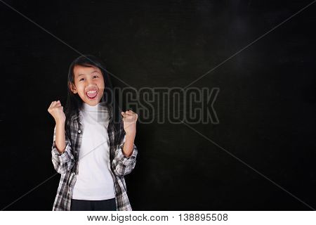 Success concept portrait of happy cute beautiful Asian girl showing enthusiastic winning gesture shout with joy of victory over blackboard