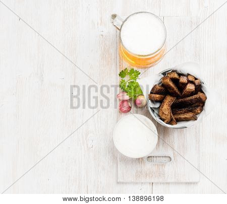 Beer snack set. Pint of pilsener in mug and rye bread croutons with garlic cream cheese sauce over white painted old wooden background, top view, copy space