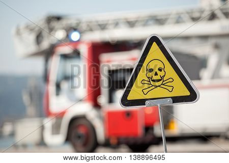 danger sign with skull and crossbones fire truck on background