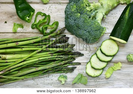 high-angle shot of some different raw green vegetables, such as green pepper, asparagus, broccoli or zucchini, on a rustic white table