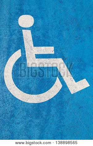 Blue handicap parking sign on asphalt for persons with disability