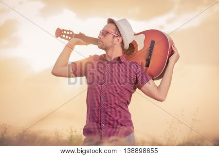 Young retro styled man holding acoustic guitar behind neck and standing in wheat field. Music, art and lifestyle concepts.