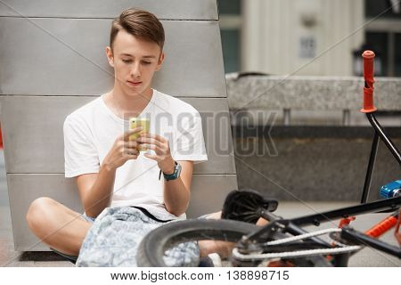 People, Travel, Technology, Leisure And Lifestyle. Handsome Caucasian Teenage Boy Texting A Message