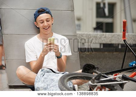 People, Technology, Leisure And Lifestyle - Happy Hipster Schoolboy Surfing The Internet Using Mobil