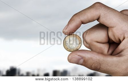 Five euro coin between fingers . Mixed media