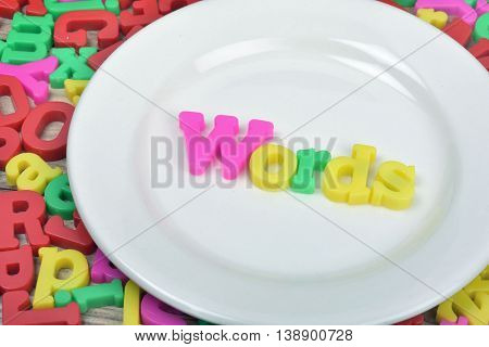 Words on white plate and magnetic letters