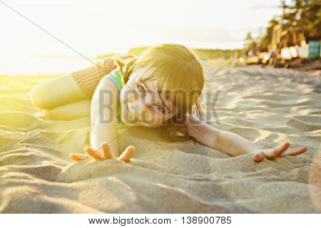 Happy little girl lying on the sand on the beach.